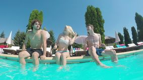 Trois amis dansant et ayant l'amusement au bord d'une piscine banque de vidéos