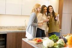 Trois amis de femmes grillant le vin blanc Images stock