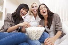 Trois amis de femmes mangeant du maïs éclaté à la maison Photographie stock libre de droits