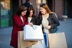 Trois amis de femmes regardant des achats ensemble Photo libre de droits