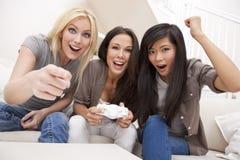 Trois amis de jeunes femmes jouant des jeux vidéo Photos stock