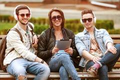 Trois amis de jeunes hommes à l'aide du comprimé Photos stock