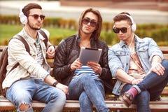 Trois amis de jeunes hommes à l'aide du comprimé Images stock