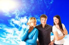 Trois amis de l'adolescence extérieurs, au-dessus du ciel bleu Photographie stock