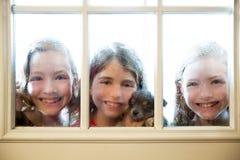 Trois amis de soeur regardant par la fenêtre pluvieuse Photographie stock libre de droits