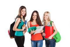 Trois amis de sourire d'étudiants avec des cahiers Image libre de droits