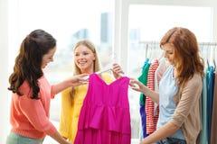Trois amis de sourire essayant sur quelques vêtements Photo libre de droits