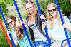 Trois amis de sourire heureux sur des oscillations au-dessus d'été Photographie stock libre de droits