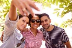 Trois amis de sourire prenant un selfie Image stock
