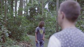 Trois amis de touristes marchent dans la forêt et des vidéos tropicales sur le petit appareil-photo d'action banque de vidéos