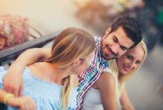 Trois amis, deux femmes et un homme, ayant l'amusement sur le banc Photo libre de droits