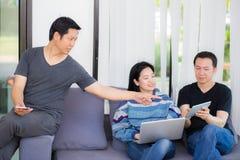 Trois amis en ligne avec les dispositifs et parler multiples Images stock
