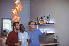 Trois amis encourageant et buvant de la bière tout en regardant la rencontre Image stock
