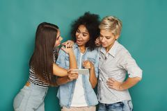 Trois amis féminins à l'aide des smartphones Images libres de droits