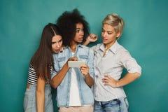 Trois amis féminins à l'aide des smartphones Image libre de droits