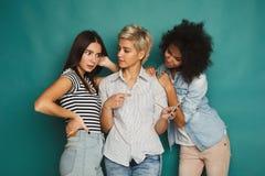 Trois amis féminins à l'aide des smartphones Image stock