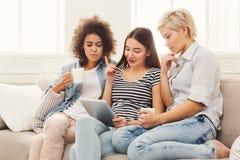Trois amis féminins à l'aide du comprimé et buvant du café Images stock