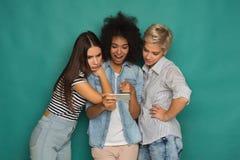 Trois amis féminins à l'aide du smartphone Images stock
