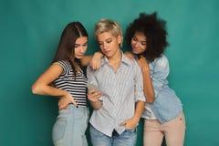 Trois amis féminins à l'aide du smartphone Photographie stock