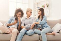 Trois amis féminins à l'aide du smartphone Photo stock