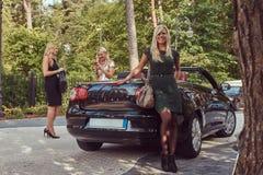 Trois amis féminins à la mode heureux tenant la voiture de luxe proche de cabriolet en parc Photographie stock libre de droits