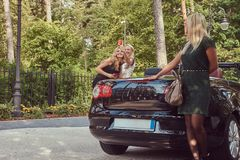 Trois amis féminins à la mode heureux tenant la voiture de luxe proche de cabriolet en parc Photo stock