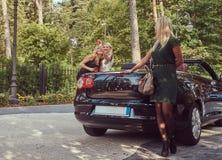 Trois amis féminins à la mode heureux tenant la voiture de luxe proche de cabriolet en parc Photos stock
