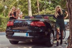 Trois amis féminins à la mode heureux tenant la voiture de luxe proche de cabriolet en parc Photographie stock