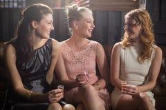 Trois amis féminins agissant l'un sur l'autre les uns avec les autres tout en ayant la tequila dans la barre Photos libres de droits