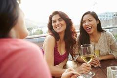 Trois amis féminins appréciant la boisson à la barre extérieure de dessus de toit Images libres de droits