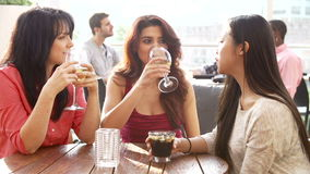 Trois amis féminins appréciant la boisson à la barre extérieure de dessus de toit clips vidéos