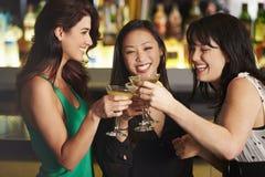 Trois amis féminins appréciant la boisson dans la barre de cocktail Photo stock