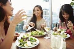 Trois amis féminins appréciant le déjeuner au restaurant de dessus de toit Image stock