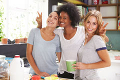 Trois amis féminins appréciant le petit déjeuner à la maison ensemble Image libre de droits