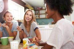 Trois amis féminins appréciant le petit déjeuner à la maison ensemble Photographie stock