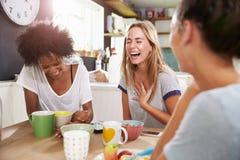Trois amis féminins appréciant le petit déjeuner à la maison ensemble Images libres de droits