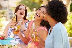 Trois amis féminins appréciant le repas à la partie extérieure Image libre de droits