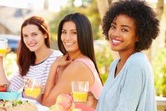 Trois amis féminins appréciant le repas à la partie extérieure Photographie stock