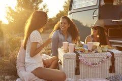 Trois amis féminins appréciant un pique-nique en leur camping-car Photo stock