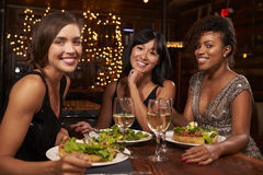 Trois amis féminins au dîner dans le restaurant regardent à l'appareil-photo Photos libres de droits