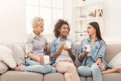 Trois amis féminins avec du café causant à la maison Photo stock