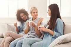 Trois amis féminins avec du café causant à la maison Image stock