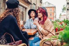 Trois amis féminins ayant des boissons en café extérieur Femmes causant et accrochant pendant la pause-café Photos libres de droits