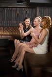 Trois amis féminins ayant la tequila dans la barre Photos libres de droits
