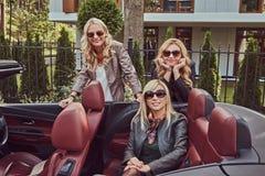 Trois amis féminins blonds portant les vêtements à la mode dans des lunettes de soleil dans une voiture de cabriolet en voyage d' Photos stock