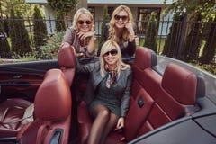 Trois amis féminins blonds portant les vêtements à la mode dans des lunettes de soleil dans une voiture de cabriolet en voyage d' Images libres de droits