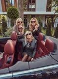 Trois amis féminins blonds portant les vêtements à la mode dans des lunettes de soleil dans une voiture de cabriolet en voyage d' Photo stock
