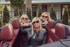 Trois amis féminins blonds portant les vêtements à la mode dans des lunettes de soleil dans une voiture de cabriolet en voyage d' Image stock
