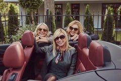 Trois amis féminins blonds portant les vêtements à la mode dans des lunettes de soleil dans une voiture de cabriolet en voyage d' Image libre de droits