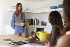 Trois amis féminins buvant du café dans la cuisine, Ibiza Image libre de droits